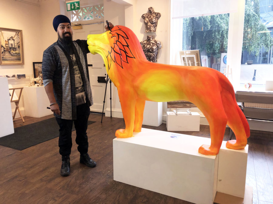 Artist live-painting lion sculpture at Windsor Gallery
